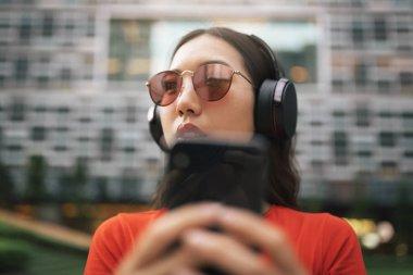 Beautiful singaporean woman listening music.
