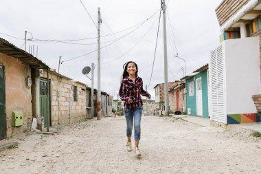 Beautiful girl running in shanty town.