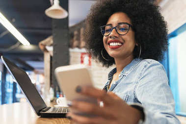 Beautiful afro american woman using mobile in the coffee shop.
