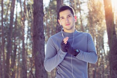 Sports man heating his hands and thinking about his trainings in forest. Winter.