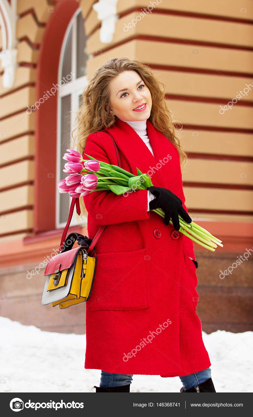 b2fda7b243d97a Schöne junge und stilvolle blonde Mädchen im roten Mantel mit Blumen.  Damen-Accessoires.
