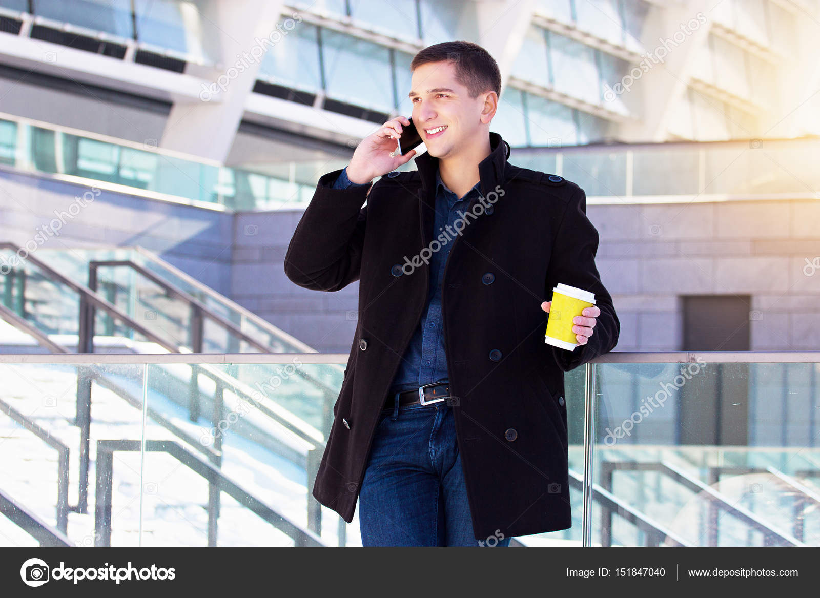 278c900ba1dd Let s talk. Portrait of young and handsome business man talking the phone  while drinking coffee