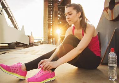Little brake during evening jog. Beautiful and young sports woman tying shoelaces on her sneakers while sitting on bridge with evening sunlight on background.