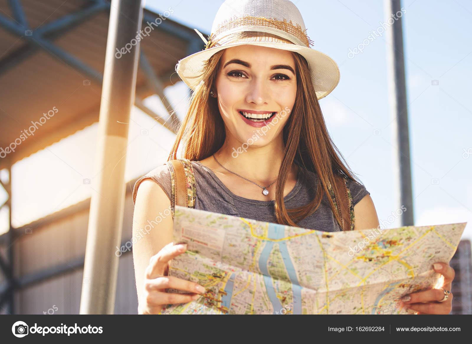 Vista de ángulo bajo de atractiva mujer joven en vestido y el sombrero  mirando a la cámara y sonriendo 751fce06135