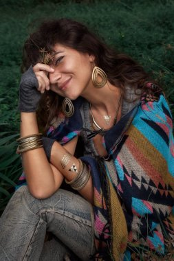 Beautiful boho woman wearing poncho sitting on green field