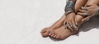 woman sitting on the sand hands and feet with ethnical accessori