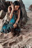 Fotografie Boho gestylte junge Hippie-Mädchen sitzen bei Sonnenuntergang am Strand