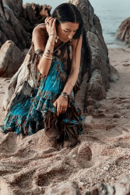 boho styled young hippie girl sitting on beach at sunset