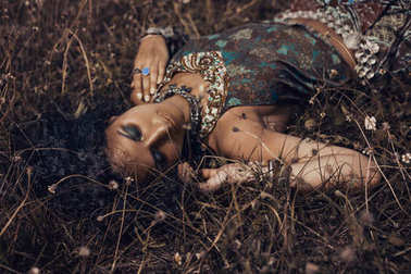 beautiful young eastern girl in ethnical jewelry lying on a gras