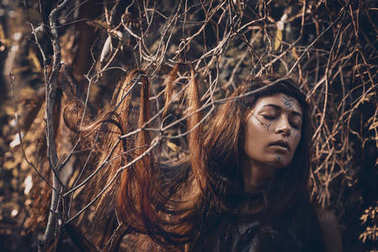 Beautiful young woman model with very long hair on branches. wit