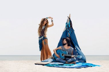 Attractive boho man playing guitar and girl dancing outdoors