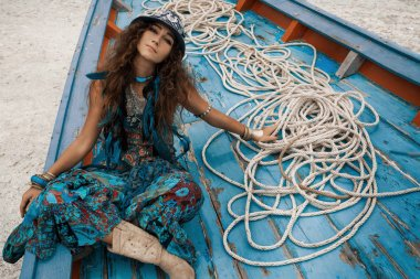 Attractive young hippie woman with guitar at boat