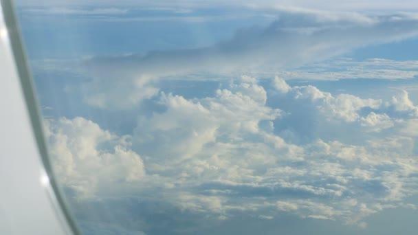 Velké bílé haldy mraky na modré obloze, Odhlédneme-li letadlo okénka