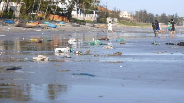 statische Aufnahme von spielenden Kindern in Defokussierung auf Strand verschmutzt durch Müll, Müll