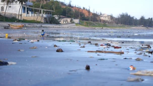 Kind spielt zwischen Plastikmüll und Müll auf Sand am Strand. Schwenk geschossen
