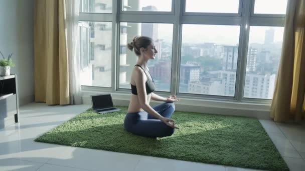Junge Mädchen, die Praxis der Meditation zu Hause mit Stadtbild Hintergrund
