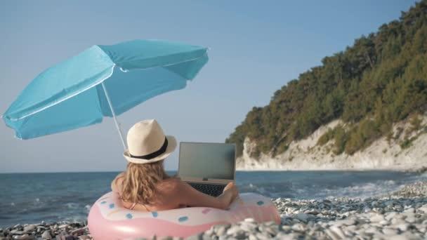 Fiatal lány dolgozik laptop szabadban a nyári vakáció