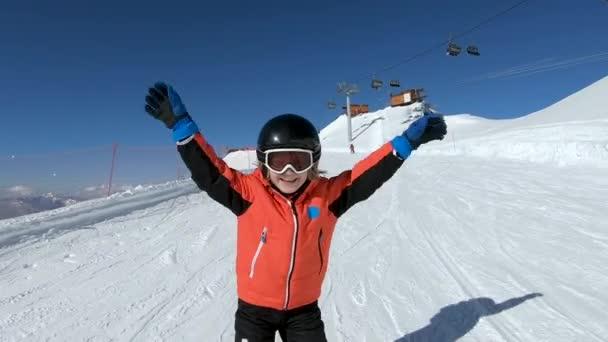 Usmívající se dětské lyžování a mávání rukou na sněhové hoře