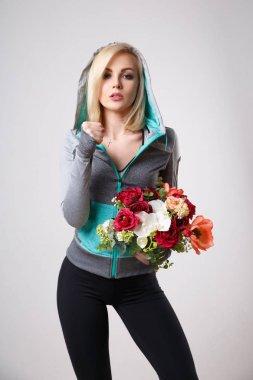 sport militant blond woman holding bouquet of flowers