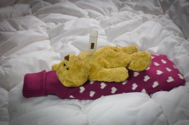 Sick teddy bear lying  with  hot-water bottle and thermometer