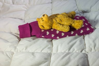 Sick teddy bear lying  with  hot-water bottle on his back