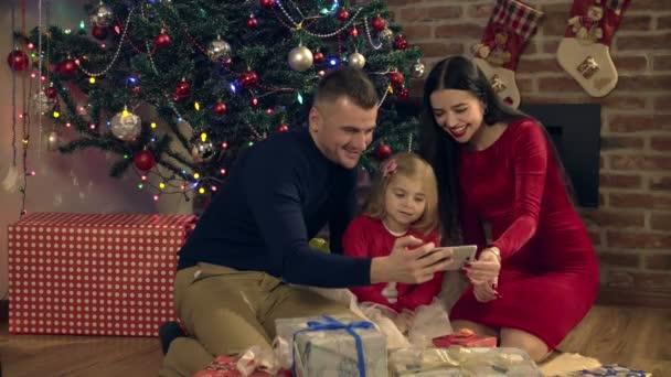 rodiče a dcera učinit společné fotografie u vánočního stromu