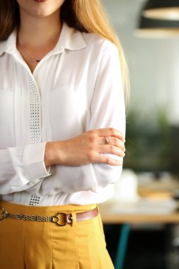 Hands of female businesswoman in blouse crossed on chest