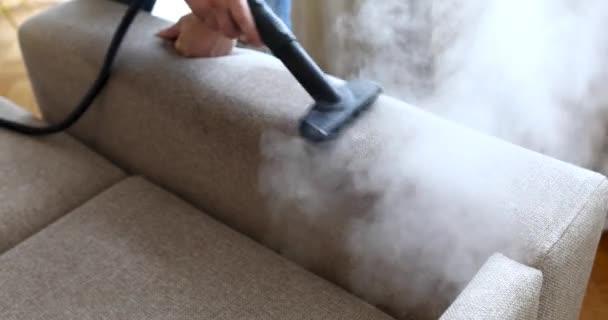 Muž hospodyně čištění rukou pohovka s kouřící kartáč detailní up