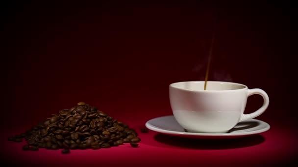 šálek kávy a kávových zrn na červeném pozadí
