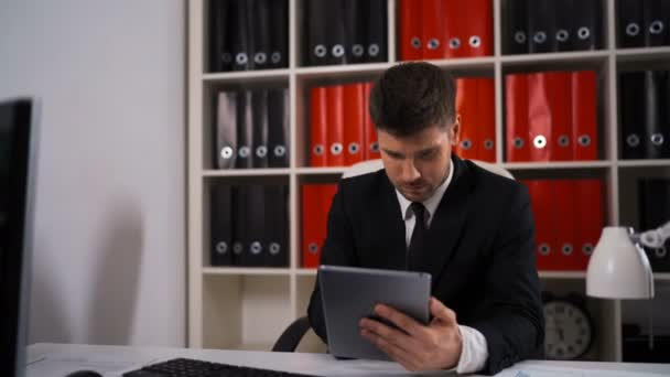 businessman writing notes from ipad in business office