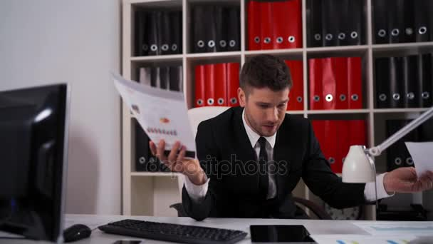 Tired businessman with documents falling asleep in office