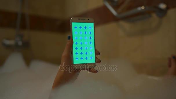 Lány használata mobiltelefon vertikális habfürdő