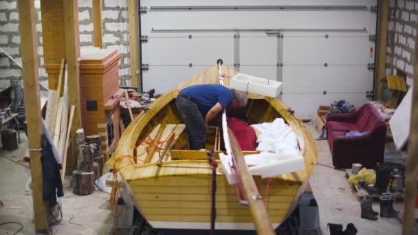 Předloha pracuje s novou dřevěnou domácí lodí v dílně. Široké