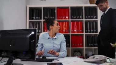 Two businesspeople in office. Woman ask man colleague to help, but he reject and go away