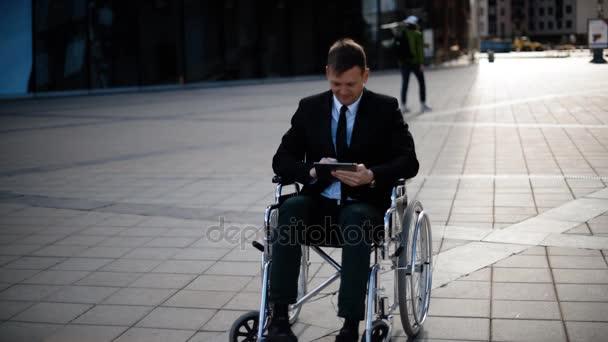 Zakázané podnikatel sedí ve vozíku venkovní a pracovat s počítačem tablet Pc