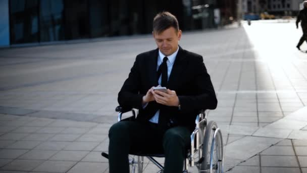 Young business man sitting on wheelchair is playing or working with his smartphone