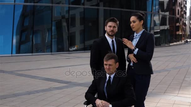Couple of business people gossip at the back of handicapped colleague