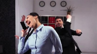 Happy colleagues dancing in office room