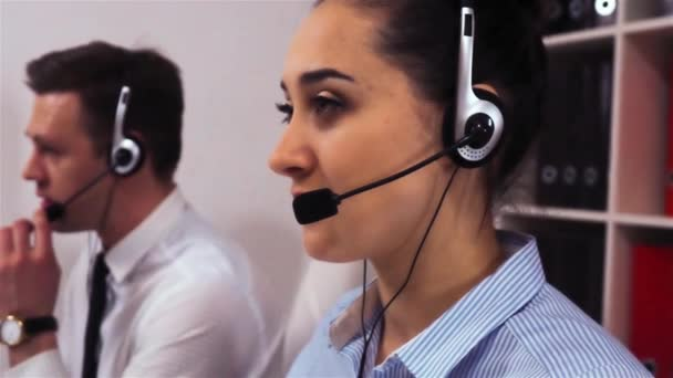 A team of call centre executives wearing headset busy on a phone with customers.