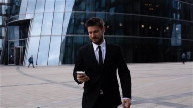 Handsome entrepreneur reading sms or messenger using app on iphone in business centre