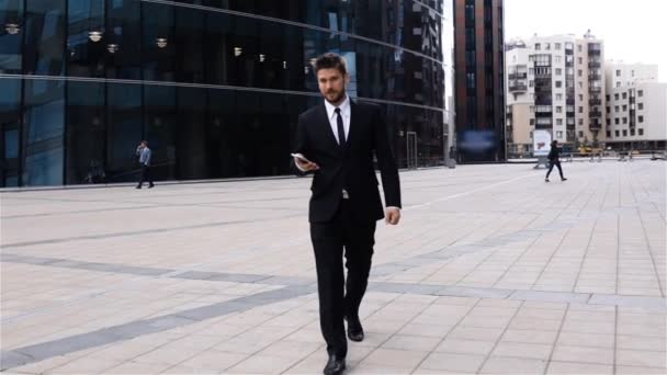 Young businessman walking, using phone in business district