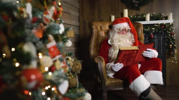 Santa Claus pulls out old red silk album near christmas tree with toys and lights