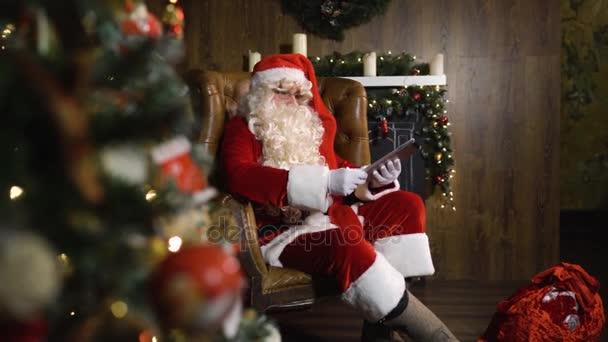 Santa Claus pracuje s iPadem