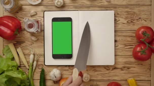 Oříznout kuchař ukazuje nožem na řádky v prázdném deníku při vaření s online receptem