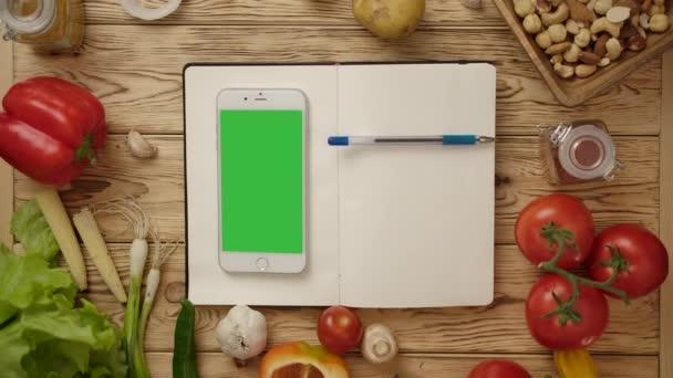 Stift rollt auf blankem Notizbuch mit Smartphone auf Küchentisch mit Gemüse