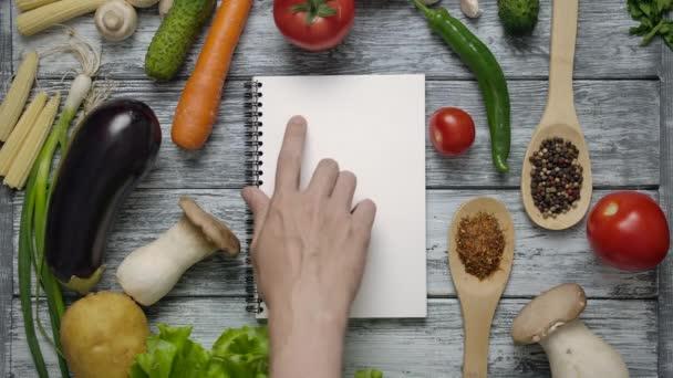 Kuchař si přečte recept tak, že přejede prstem po bílém prostěradle v zápisníku