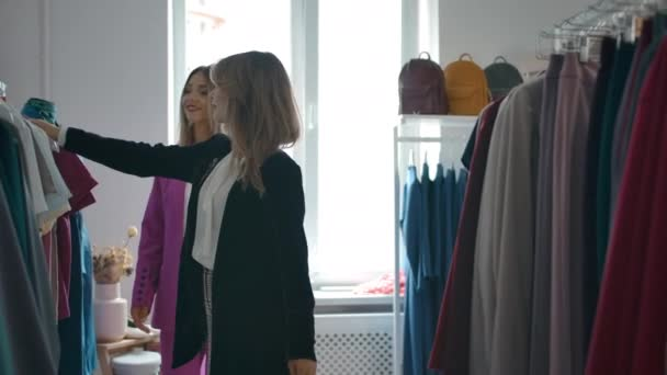 Mladé ženy vybírají oblečení v obchodě spolu.