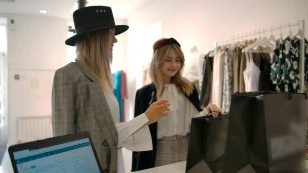 Fiatal nők fizetik a boltban történő vásárlást.