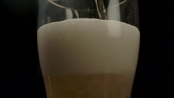 Glass slowly being filled with beer.