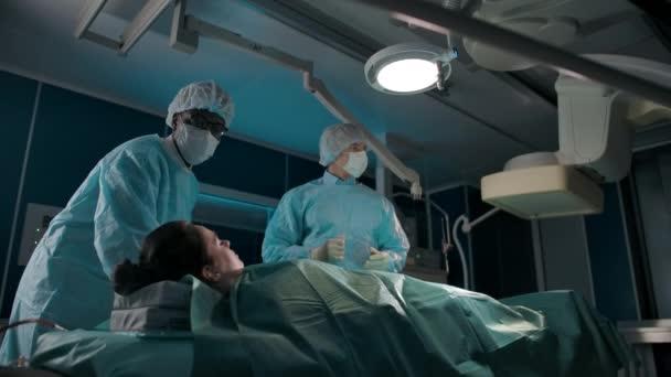 Ein dunkelhäutiger Arzt bewegt einen Operationstisch mit einer kaukasischen Patientin